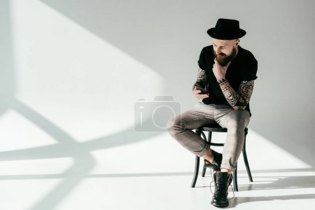 handsome bearded tattooed man sitting on chair and looking at smartphone on white