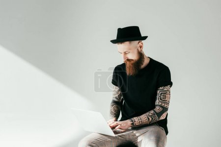 handsome bearded tattooed man using laptop on white