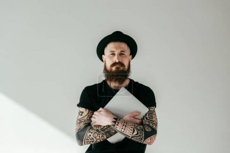 handsome bearded tattooed man hugging laptop and looking at camera on white