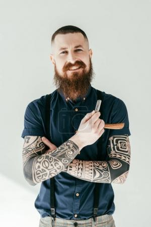 Photo for Smiling tattooed man holding razor and looking at camera isolated on white - Royalty Free Image