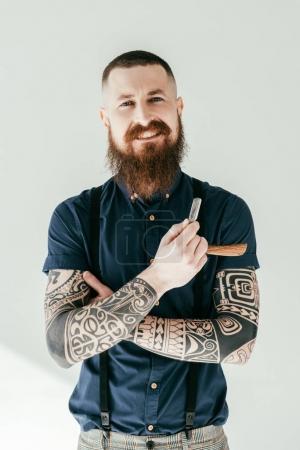 Photo pour Homme tatoué souriant tenant rasoir et regardant la caméra isolée sur blanc - image libre de droit