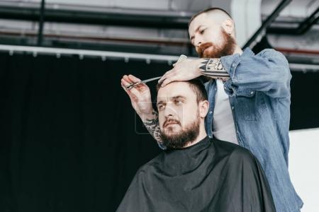 Photo pour Vue de dessous du coiffeur coupe les cheveux du client au salon de coiffure - image libre de droit