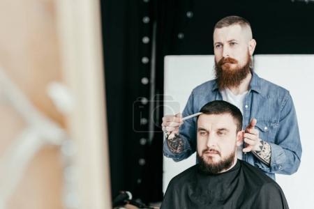 Photo pour Coiffeur regardant la coupe de cheveux du client dans le miroir au salon de coiffure - image libre de droit