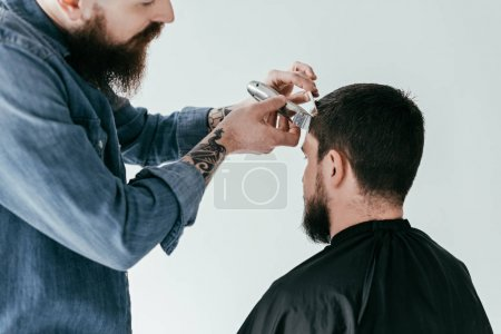 cropped image of barber shaving hair at barbershop isolated on white