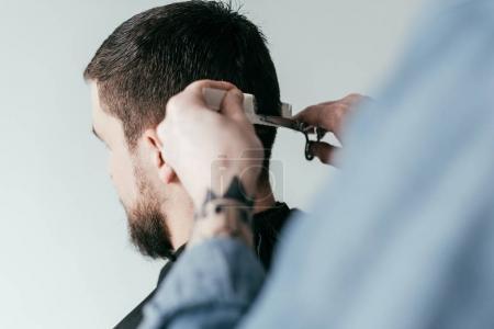 Photo pour Image recadrée de coiffeur coupe les cheveux du client au salon de coiffure isolé sur blanc - image libre de droit