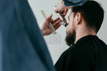 cropped image of barber trimming customer beard at barbershop