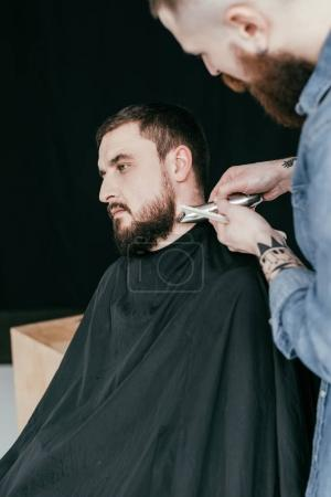 barber trimming customer beard at barbershop