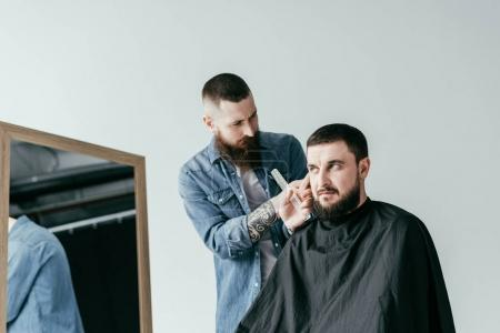 bearded barber shaving customer hair at barbershop isolated on white