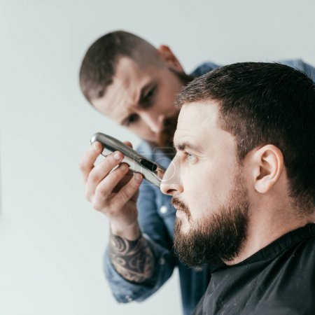 side view of barber trimming customer beard at barbershop isolated on white