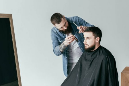 barber trimming handsome customer beard at barbershop isolated on white