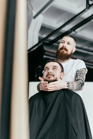 Photo pour Coiffeur style client barbe et en regardant le miroir au salon de coiffure - image libre de droit