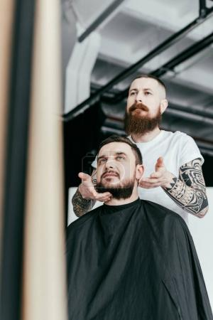 barber styling customer beard at barbershop
