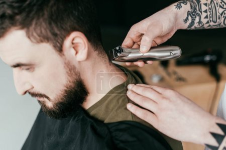 cropped image of barber shaving customer hair at barbershop
