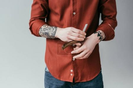 cropped image of tattooed barber holding razor isolated on white