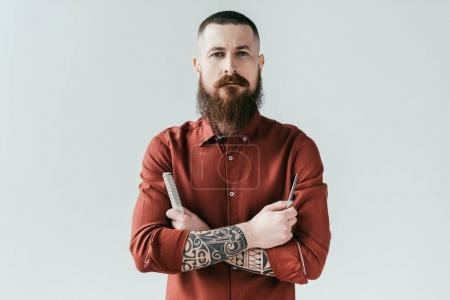 Photo for Bearded handsome barber holding comb and scissors and looking at camera isolated on white - Royalty Free Image