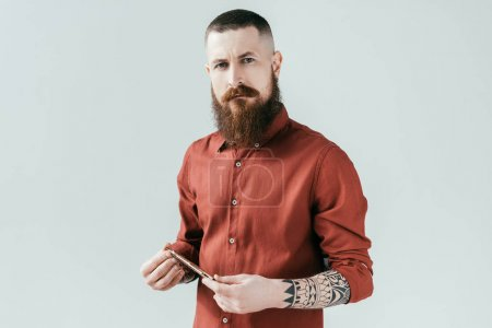 Photo for Bearded handsome barber holding razor and looking at camera isolated on white - Royalty Free Image