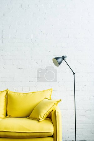 Yellow leather couch and floor lamp in front of brick wall