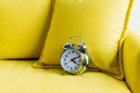 Close up view of metalic alarm clock on yellow couch