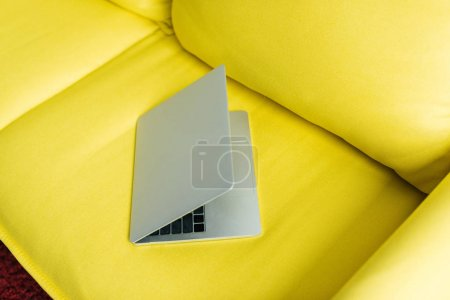 Half-closed laptop on yellow leather couch, minimalistic conception