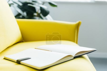 Photo for Empty textbook pages with pencil on yellow leather couch - Royalty Free Image