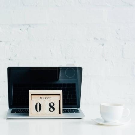 Closeup view of wooden calendar with date of 8 march on laptop and cup beside