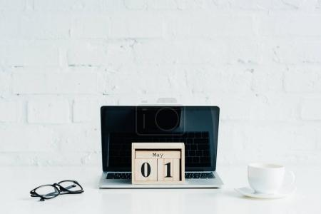 Wooden calendar on laptop with blank screen, eyeglasses and cup