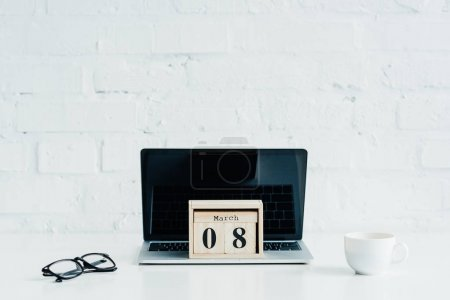 Wooden calendar with date of 8 march on laptop, international womens day concept