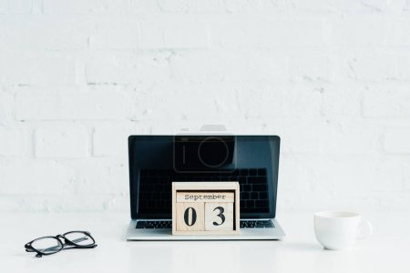 Wooden calendar on laptop with blank screen, eyeglasses and cup on white surface