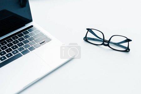 Foto de Ordenador portátil con pantalla en blanco y anteojos al lado, de concepción minimalista - Imagen libre de derechos