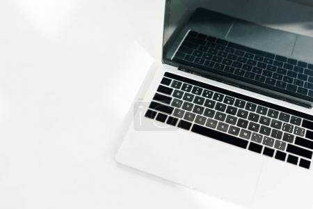 Laptop with blank screen on white surface