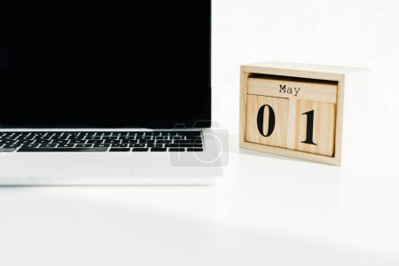 Laptop and wooden calendar on white surface