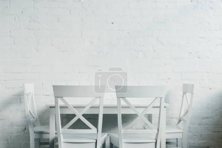 Interior of dinner room with wooden table and chairs in front of brick wall