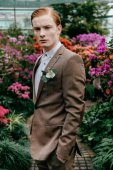 portrait of pensive stylish man with red hair in suit standing glasshouse