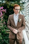 portrait of stylish man with red hair in suit and eyeglasses looking away in greenhouse