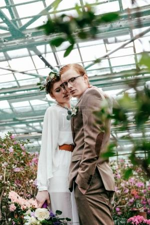 portrait of stylish bride and groom in greenhouse