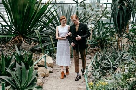 romantic bride and groom walking in greenhouse