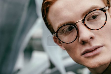 headshot of stylish man with red hair in eyeglasses looking away