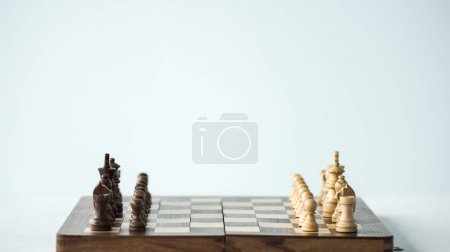 Chess board with chess pieces set for new game isolated on white