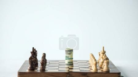 Chess board with cash and chess pieces isolated on white