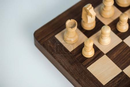 Cropped image of chess board with white chees pieces on white surface