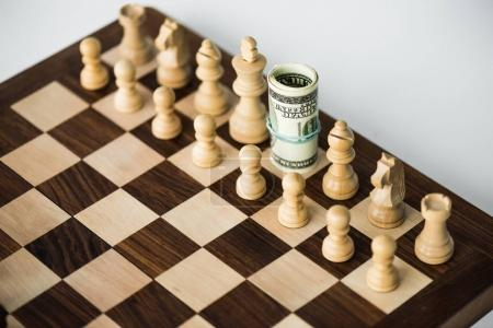 Chess board with cash and white chess pieces on white surface