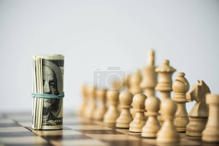 Chess pieces and rolled up cash on chess board isolated on white
