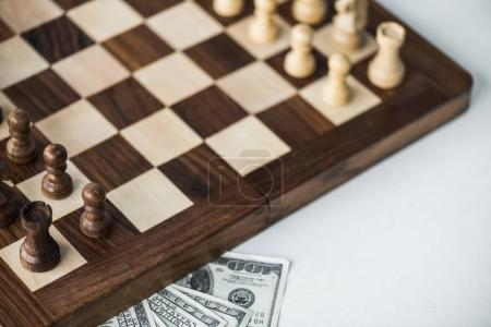 Cropped view of chess board with chess pieces and dollar banknotes on white surface
