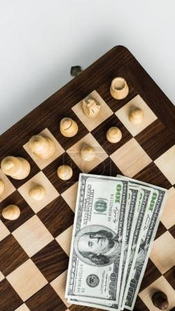 Top view of chess board with dollar banknotes and chess pieces on white surface
