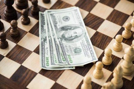 Photo pour Bouchent la vue des billets de dollar sur l'échiquier avec figures set - image libre de droit