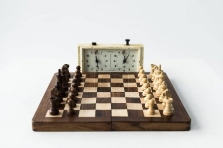 Chess clock and board with chess pieces isolated on white