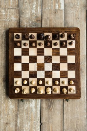 Top view of chess board with chess pieces set for new game on wooden surface