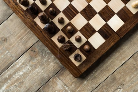 Cropped image of chess board with chess pieces on wooden surface