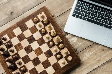 Laptop and chess board with figures on rustic wooden surface