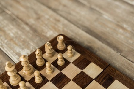 Cropped view of chess board with white chess pieces on rustic wooden surface